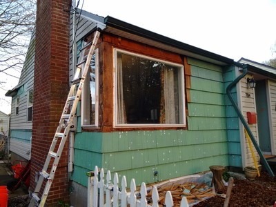 After removing shingles from the corner between the two windows, patching nail holes, and one coat of primer. The vinyl removed back past the chimney was for cellulose insulation we had blown into the wall cavities from the outside.